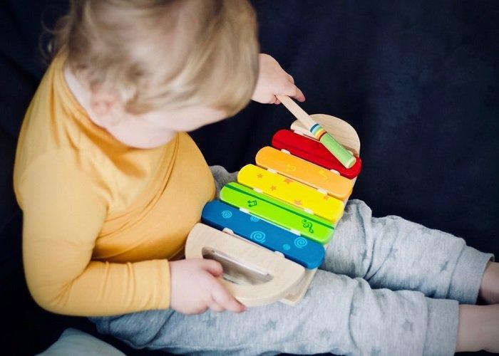 Em bé tập trung chơi đàn.