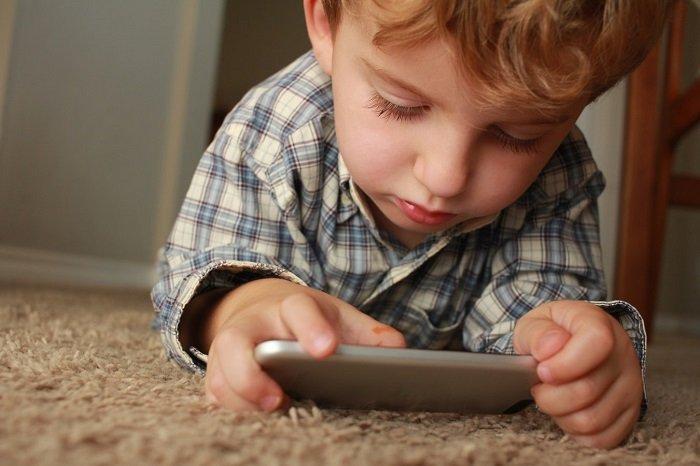 Em bé tập trung xem điện thoại.