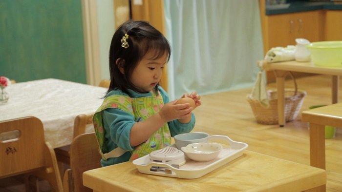 Dạy con tự lập bằng cách cho em bé ngồi tự bóc trứng.