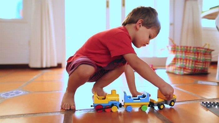 Em bé tự chơi ô tô đồ chơi.