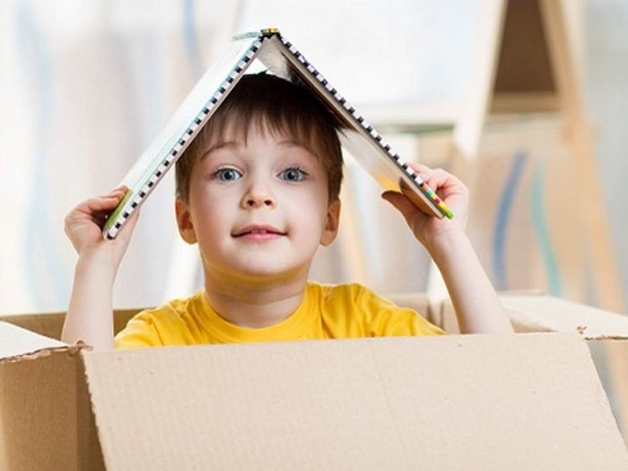 Em bé trai ngồi trong hộp giấy.