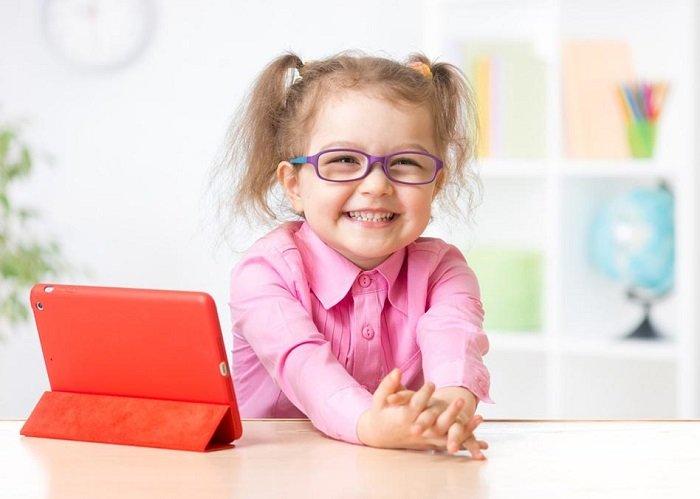 Bé gái cười vui bên iPad.