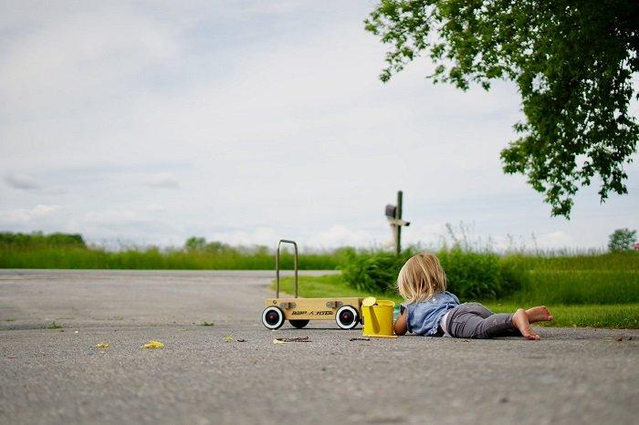 Em bé chơi một mình với ô tô.