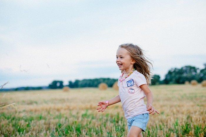 Em bé vui chạy trên đồng.