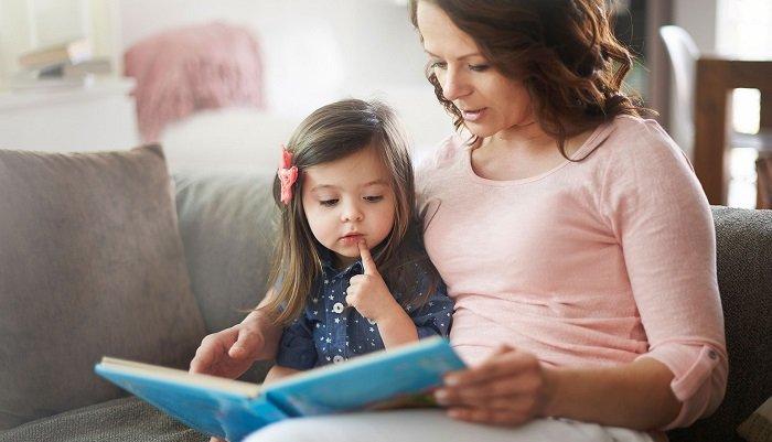 mẹ đọc sách cùng con gái trên sofa