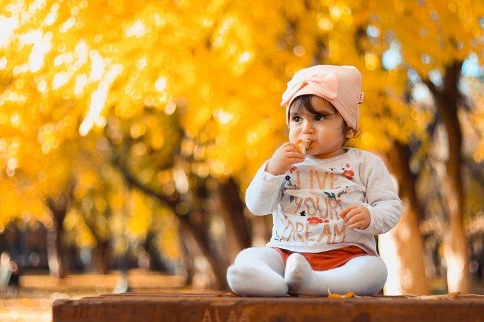 em bé ngồi ăn mật ong.