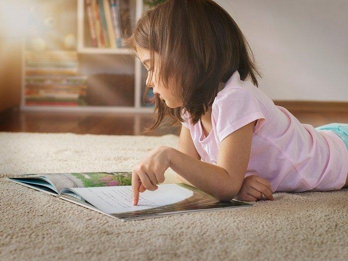 bé gái đọc sách trên sàn nhà
