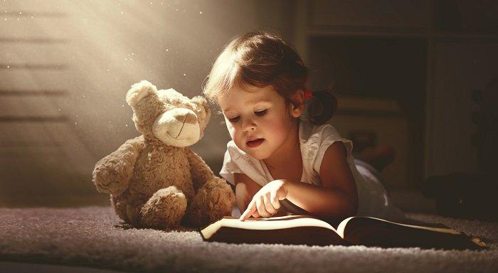 bé gái đọc sách cùng gấu bông