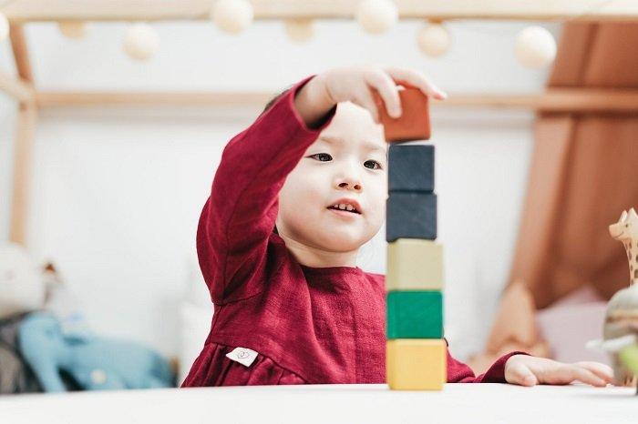 Em bé ngồi chơi xếp tháp một mình.
