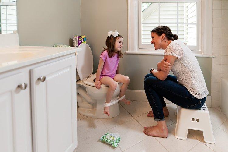 Em bé ngồi đi vệ sinh cùng mẹ.