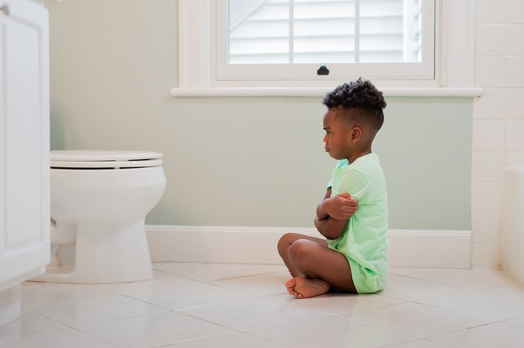 Em bé không muốn đi vệ sinh.