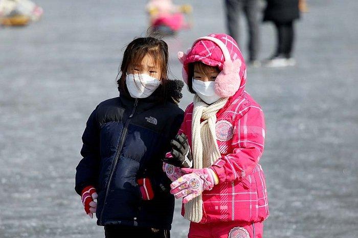 Hai bé đeo khẩu trang vì trẻ em có dễ nhiễm Covid-19