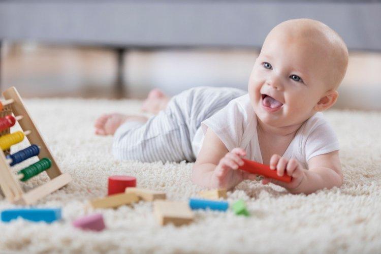 trẻ em 10 tháng tuổi biết làm gì? biết cầm nắm đồ chơi, bé trườn bò khi đang chơi