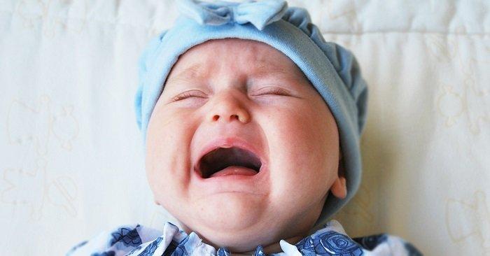 bé sơ sinh đội mũ xanh đang khóc