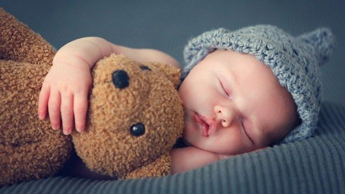 bé sơ sinh ôm gấu ngủ