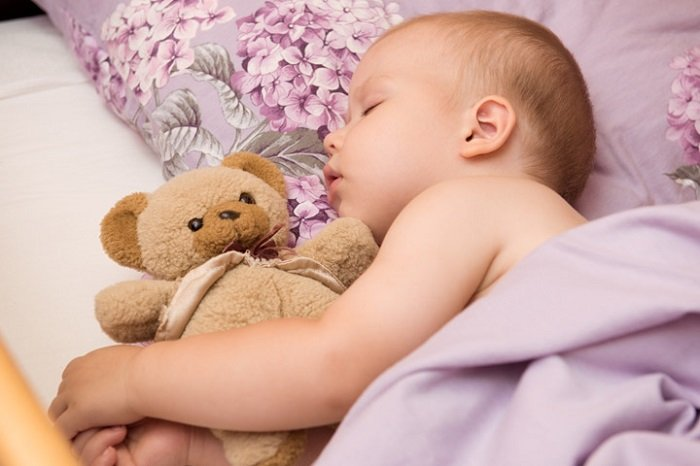 Em bé ôm gấu bông ngủ ngon.