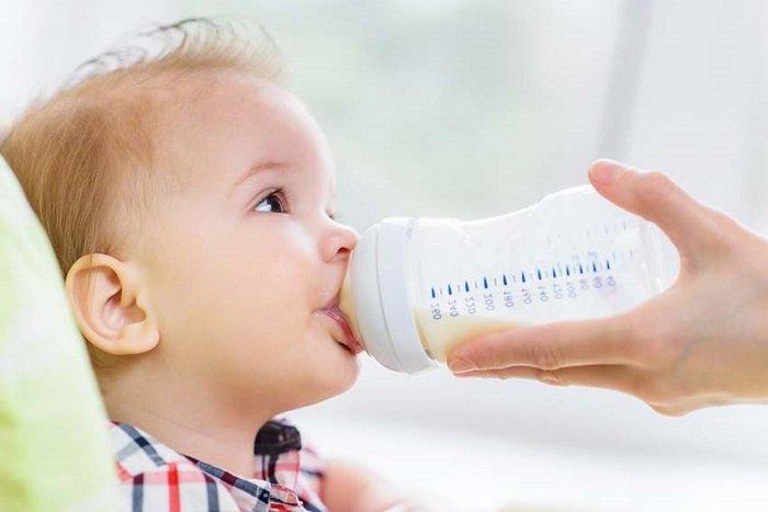bé 1 tuổi uống sữa trong bình