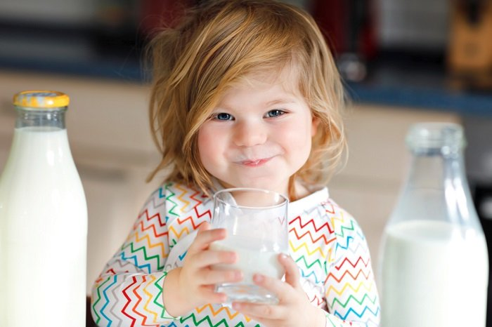 bé gái uống sữa trong cốc