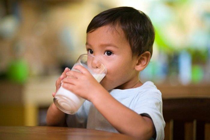 bé trai uống sữa trong cốc