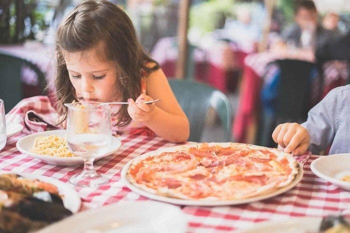 bé gái tự ăn mì trên bàn ăn, ngôn ngữ cơ thể