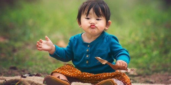 bé 2 tuổi ngồi trên đồng cỏ
