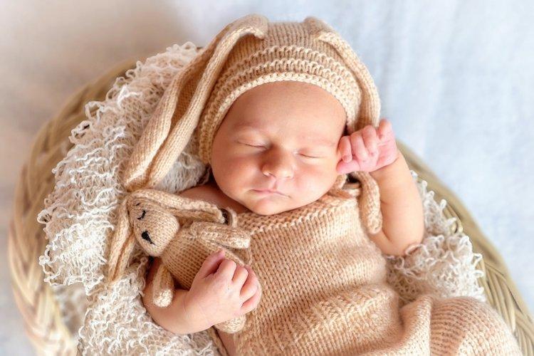 bé sơ sinh ôm gấu bông nằm ngủ