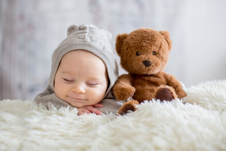 bé sơ sinh nằm ngủ bên cạnh gấu bông thân yêu
