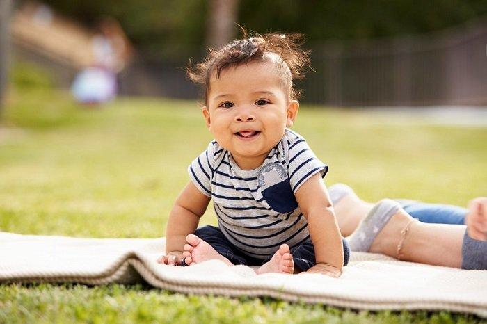 bé ngồi trên nền cỏ