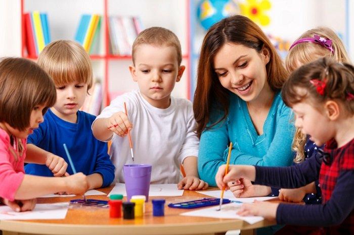 Em bé ngồi vẽ cùng giáo viên.