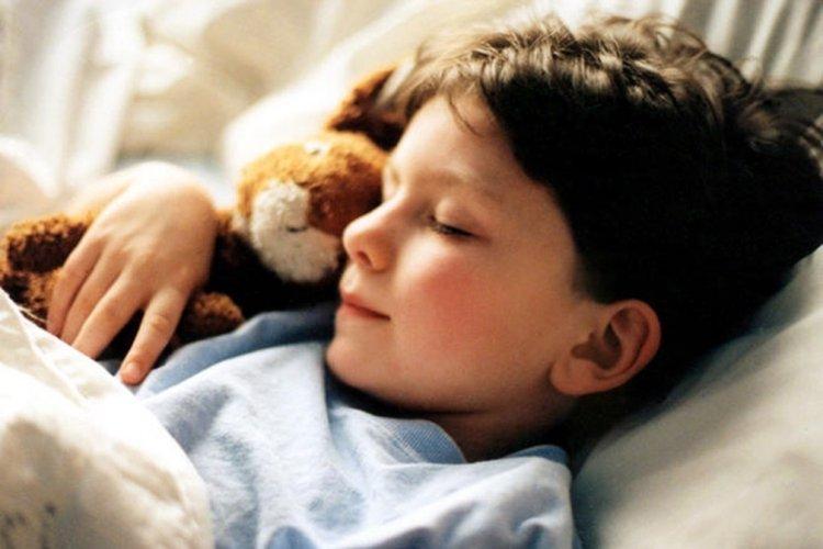 bé trai ôm gấu bông đi ngủ, thời gian ngủ của trẻ lúc này là 10-12 tiếng