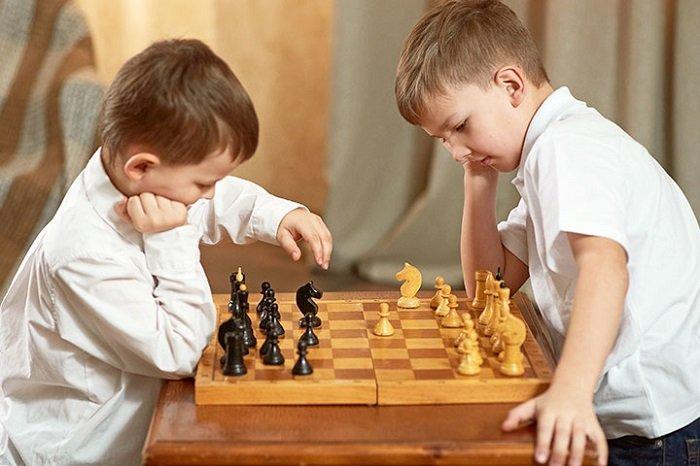 Hai em bé chơi cờ vua cùng nhau.