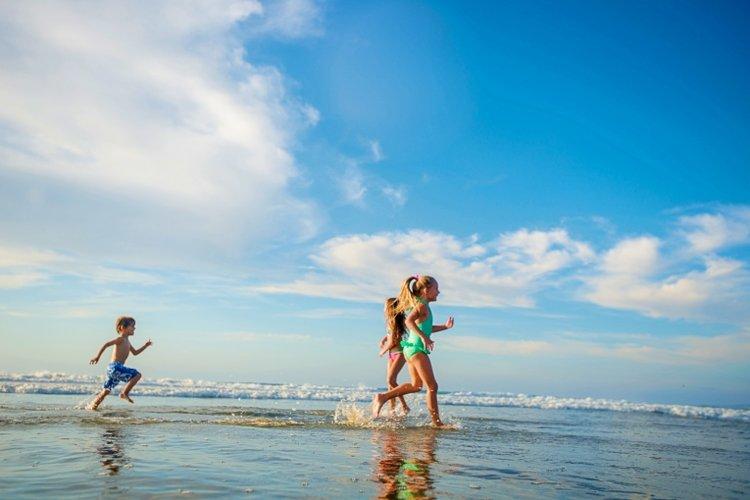 bé đi tắm biển, chạy nhảy gần bờ biển