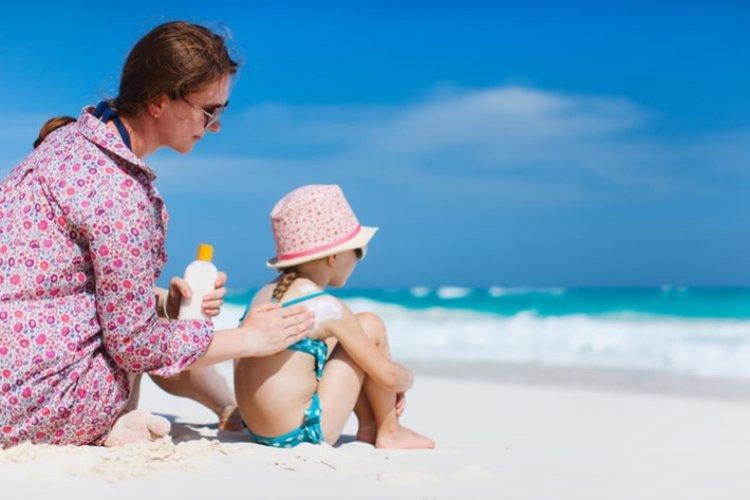 mẹ thoa kem chống nắng cho bé đi tắm biển an toàn