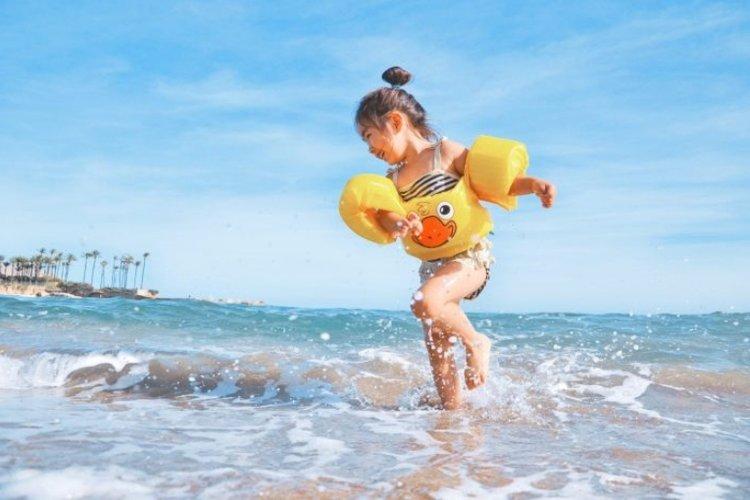bé đi tắm biển mặc áo phao an toàn