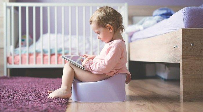 Em bé ngồi bô dùng máy tính.