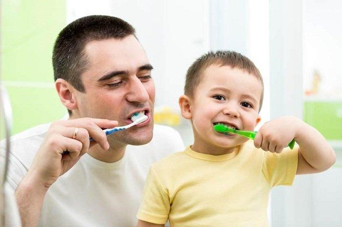 Bố dạy bé đánh răng đúng cách.