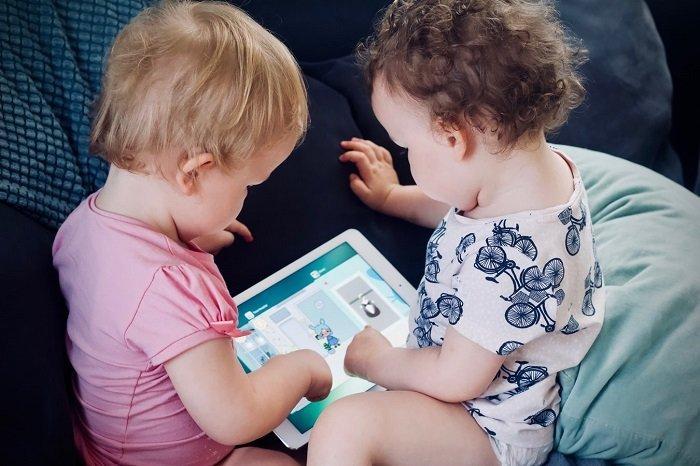 Hai em bé chơi thiết bị điện tử