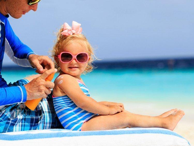 mẹ thoa kem chống nắng cho trẻ, cho trẻ đeo kính râm bảo vệ mắt khỏi ánh nắng mặt trời
