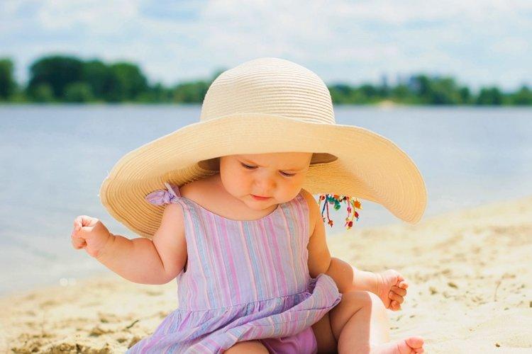 bố mẹ bảo vệ trẻ khỏi ánh nắng mặt trời bằng cách cho trẻ đội mũ rộng vành