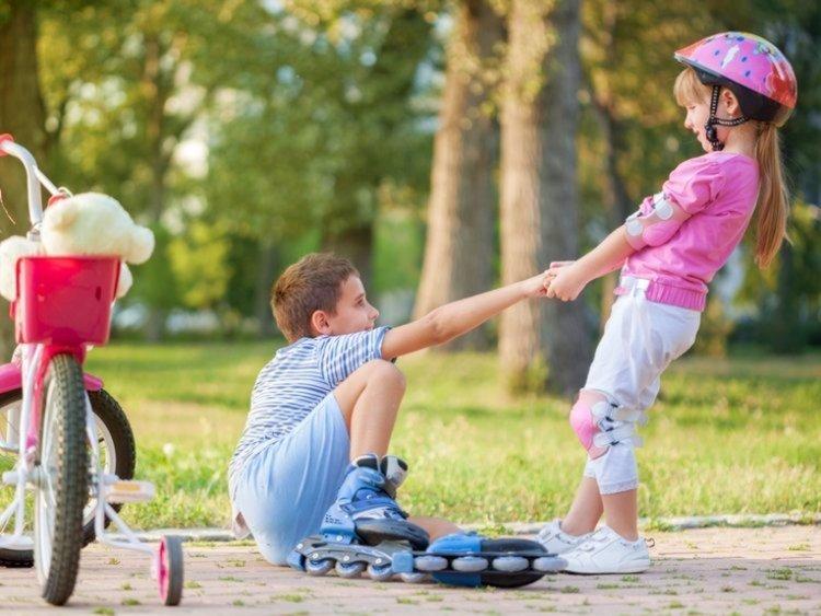 bé gái áo hồng giúp đỡ bạn trượt patin bị ngã
