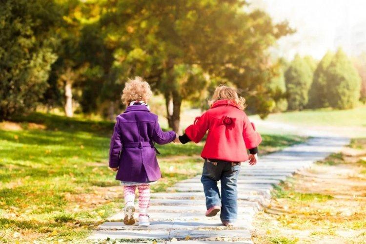 2 bé gái dắt tay nhau đi dạo bộ, đây là hoạt động vui chơi giúp trẻ phát triển kỹ năng vận động
